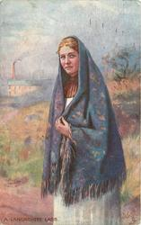 girl with blue shawl over head, factory in distance.