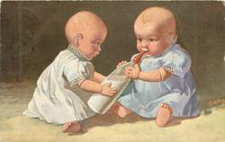 two personised baby dolls sit facing one another, both holding, and one sucking at, bottle of milk