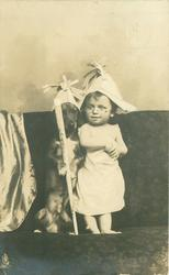 spectacled baby standing on couch with dog propped on right, both wear paper hats