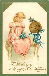 TO WISH YOU A HAPPY CHRISTMAS  girl in pink sits talking to a personalised christmas pudding