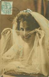 head & shoulder study of artiste in wedding dress holding veil across her face