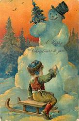 A HAPPY CHRISTMAS TO YOU  child sitting on toboggan writing on snowman