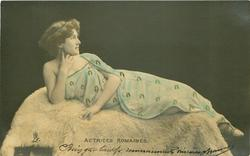 actress reclines on fur covered couch, facing front looking right, her right hand under her chin