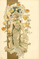woman in grey & yellow, stands holding very long stemmed chrysanthemums