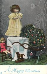 A HAPPY CHRISTMAS  girl in yellow dress stands on table,  Xmas tree in cart