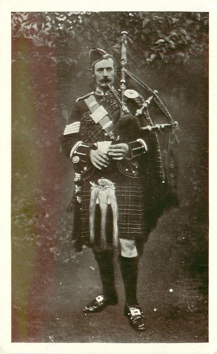piper in full regalia, black stockings, faces front