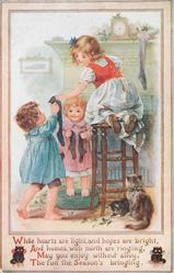 three children hanging up stockings, cats on floor