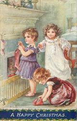 A HAPPY CHRISTMAS  three children preparing to hang up Christmas stockings