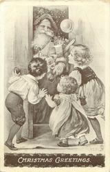 CHRISTMAS GREETINGS  three children greet Santa coming through  door with toys