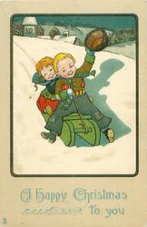A HAPPY CHRISTMAS TO YOU girl and boy toboggan down hill