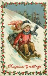 CHRISTMAS GREETINGS  boy & girl on sled come down snowy slope, holly border