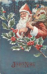 Santa in red robe and hood carries sack of toys, holly branch front, blue card