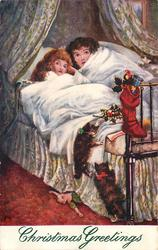 two children in bed watching for santa, two kittens climb
