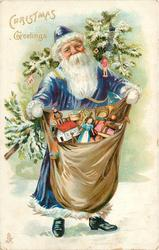 CHRISTMAS GREETING  blue robed Santa holds sack of toys, Christmas tree on his back