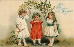 A MERRY CHRISTMAS  girl wearing red stands under mistletoe & holly held up by two other girls