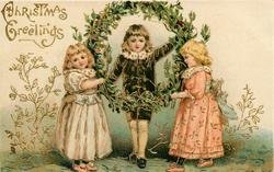 CHRISTMAS GREETINGS  boy in black suit stands in holly wreath held up by two girls