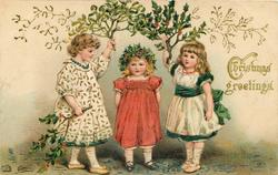CHRISTMAS GREETINGS  girl wearing red stands under mistletoe & holly held up by two other girls
