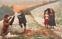 children building snowman, mother & daughter observe