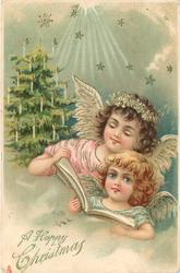 A HAPPY CHRISTMAS  two angels read, light above, tree back left