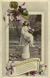A HAPPY CHRISTMAS  girl sits on pedestal holding flowers, violets around