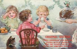 three children sit at table awaiting Xmas pudding