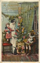 A HAPPY CHRISTMAS  mother & small girl left, girl standing on chair, boy right sitting on box, tree in centre, black doll