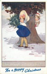 FOR A HAPPY CHRISTMAS (in blue at base)  boy peeks at girl carrying mistletoe