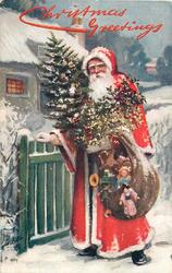 CHRISTMAS GREETINGS  Santa carrying sack of toys & tree stands with hand on gate