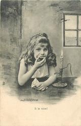 young girl sitting eating at table by candlelight