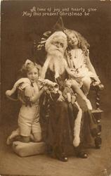 Santa seated in chair, boy & girl on either side, boy plays trumpet
