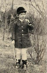 boy in fox-hunting outfit, whip in right hand, blows horn