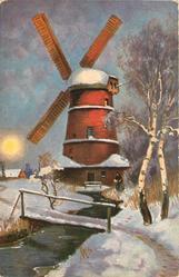 winter scene, woman in front of mill, path and bridge cross stream which runs forward, silver birches to right