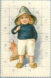boy in blue jersey, with toy sailing boat