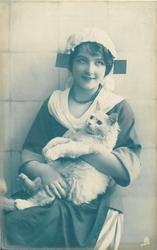 seated Dutch girl facing left/front, looking up, cuddles white cat held lying back on her lap