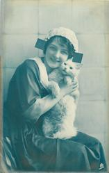 seated Dutch girl facing right, looking front, cuddles white cat under her chin as it stands up on her lap