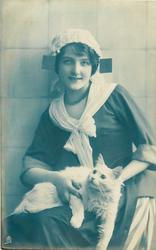 seated Dutch girl facing slightly left, looking up/front, holds white cat held lyng on her lap looking up/left