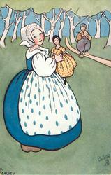 girl in blue holding doll in yellow with red polka dots, boy behind on path