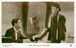 IVOR NOVELLO AND SAM KERN  man left sits, other man right stands, both hold the same paper