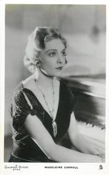 MADELEINE CARROLL  seated hands in lap, but not visible, piano right