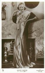 """WENDY BARRIE IN """"IT'S A BOY""""  full length study, she wears silk dress, smiles"""