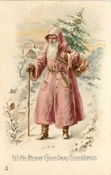 WITH MERRY CHRISTMAS GREETINGS purple robed Santa walks front/left in snow, carrying tree