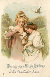 WISHING YOU A HAPPY CHRISTMAS  two girls stand side by side dove on hand of girl to right, another dove flies