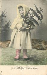 A HAPPY CHRISTMAS  girl stands facing front in winter clothes holding  Xmas tree