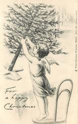 FOR A HAPPY CHRISTMAS angel stands on chair holding tree