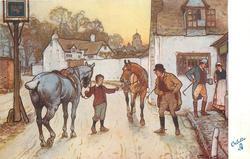 boy holding two horses outside inn