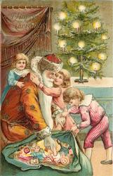 A HAPPY CHRISTMAS  Santa shows children his sack of toys, girl embraces him, tree on table