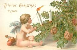 A HAPPY CHRISTMAS TO YOU nude baby angel sits trying to blow out candle on xmas tree, wallnuts hang, apples on ground
