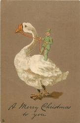 A MERRY CHRISTMAS TO YOU  manniken in green riding large white goose which faces left