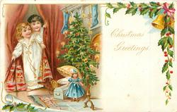 CHRISTMAS GREETINGS  2 children enter through deep-red curtains, tree & toys before fire-place, holly & bell upper right