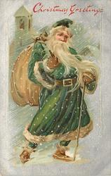 CHRISTMAS GREETINGS  full length green-robed santa with cane in left hand, bag over shoulder